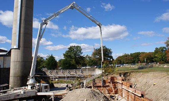 Concrete boom truck fills the forms for the containment wall