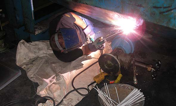 welder is repairing a steel fuel storage tank