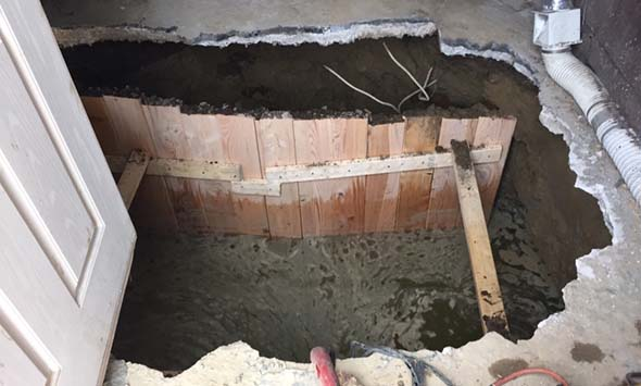 Excavation with shoring inside of backyard shed