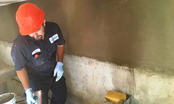 Technician installing a concrete liner inside an underground tank