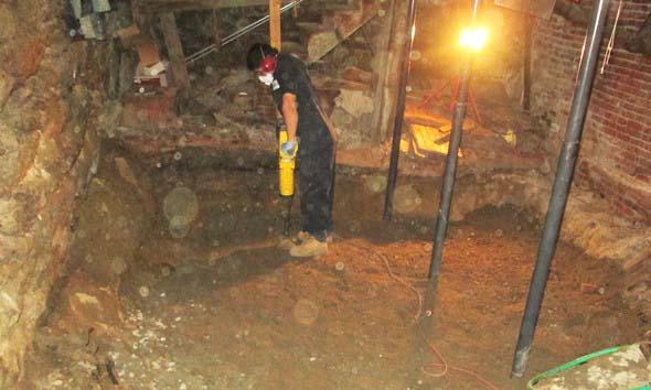Technician advancing a soil boring in basement of apartment building