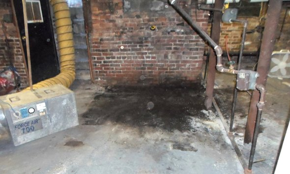 Negative air machine removes vapors from oil stained basement floor