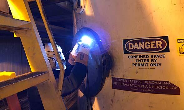 Welder is replacing the steel hatch on this pressure vessel