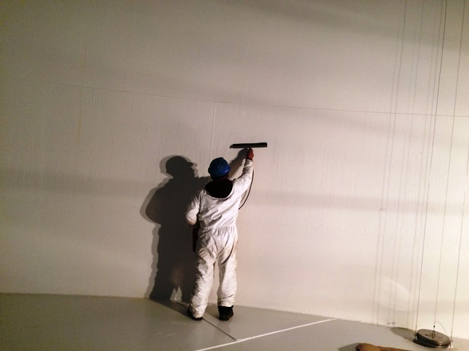 A crewman performing a paint coating inspection