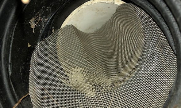 A closeup of the damaged screen on the outlet of the overflow pipe