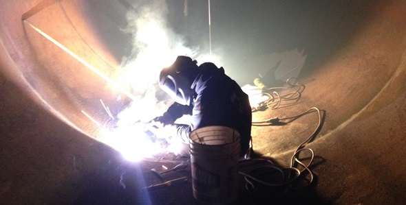 API Certified welder adding a steel patch over a corroded area