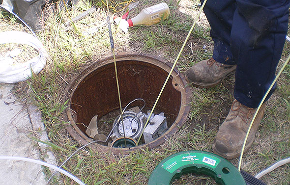 Photo of an annular space sensor being restored to the proper location.