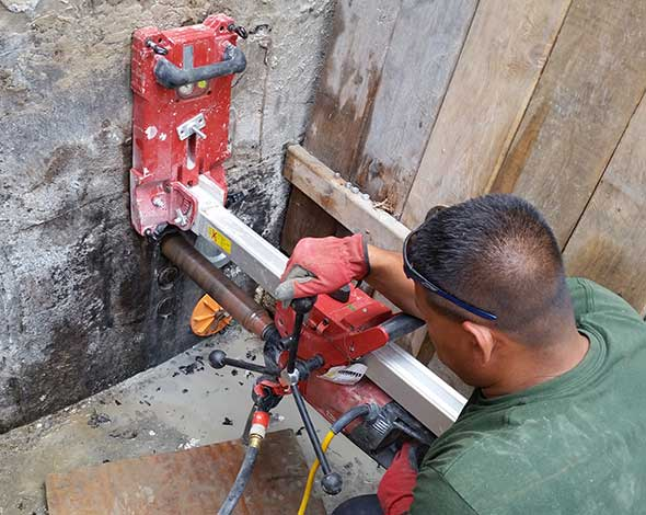 Photo of drilling holes for pipe access through a foundation