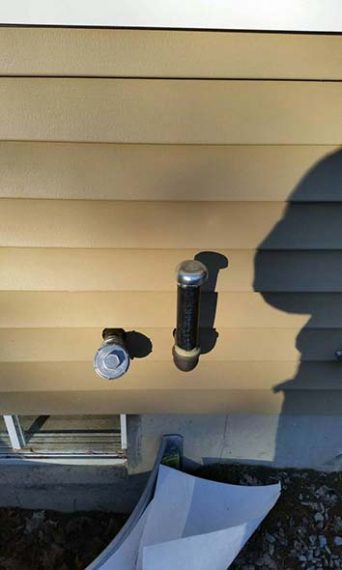 Fill and vent pipes installed through wood siding