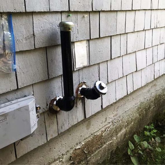 Oil fill and vent pipes on the home exterior